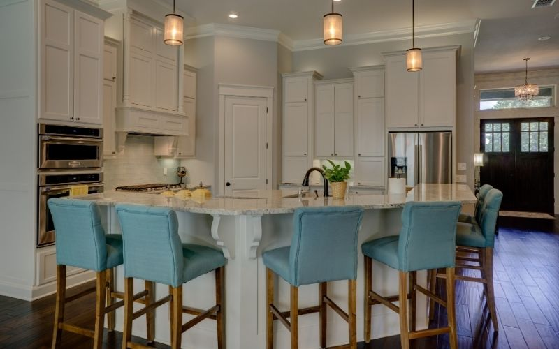 Dark wood floor with white kitchen and light colored furniture