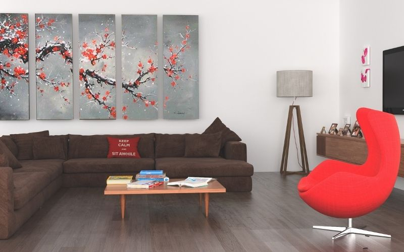Dark wood floor with bright red furniture and pops of white